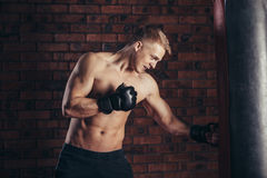 A young boxer in black gloves with a naked torso work out strikes on punching bag. Royalty Free Stock Images