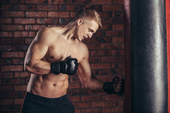 A young boxer in black gloves with a naked torso work out strikes on punching bag. Stock Images