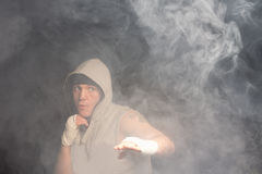 Young boxer fighting in a dark smoky room Stock Photos