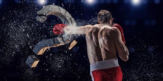 Strong enough to challenge it. Mixed media. Young boxer man crashing concrete question mark. Mixed media Royalty Free Stock Photography