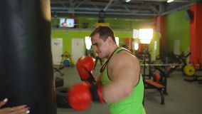 Young boxer man practicing on a punching bag stock footage
