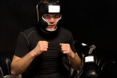 Young boxer psyching himself up as he dresses Royalty Free Stock Photo
