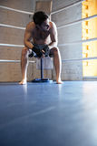 Young boxer sitting in the corner of boxing ring Stock Photo