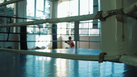 The young boxer training with punching bag in gym look through a ring. Sparring of two young boxers look through a ring stock video