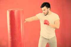 Young boxer training on a punching bag warm filter applied Royalty Free Stock Photo