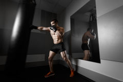 Young boxer trains on punching bag Stock Images