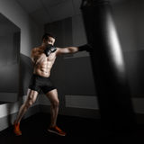 Young boxer trains on punching bag Stock Photo