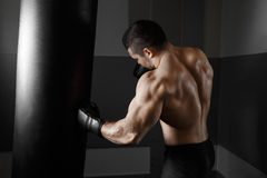 Young boxer trains on punching bag Royalty Free Stock Image