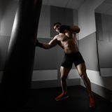 Young boxer trains on punching bag Stock Photos