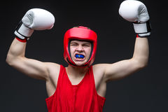 Young boxer winner. Teenage boxer in red form and white boxing gloves with hands up. Young champion. Studio shot on black background stock photos
