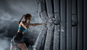 Young boxer woman . Mixed media. Determined boxer woman breaking concrete wall. Mixed media stock photos