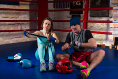 Young boxing couple preparing bandages for fight near lying boxing gloves and helmet. In regular boxing ring in a gym stock photography