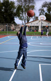 Young boy 11. Young boy airborne while shooting a basketball stock images