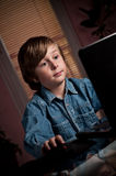 Young boy. Playing computer game on laptop Stock Photo