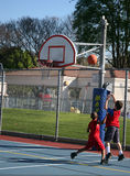 Young boy 19. Two young boys shooting some hoops at the park Stock Photos