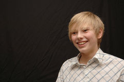 Young boy. A 12 years old male youth in front of a black background stock photos