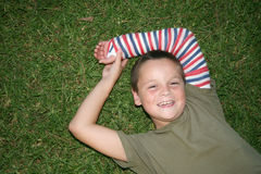 Young boy 22. Young boy laying on the grass with a cast on his arm Royalty Free Stock Image