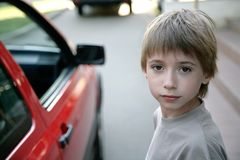 Young boy. Portrait of youn boy standing before red car Royalty Free Stock Photography