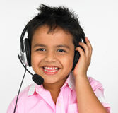 Young boy. Smiling and talking into the headphone Stock Photos