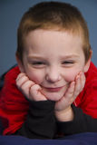 Young Boy 8081. Young boy leaning on elbows resting face on hands Royalty Free Stock Photos