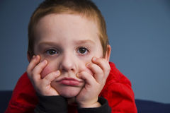 Young Boy 8084. Young boy leaning on elbows resting face on hands looking thoughtful Royalty Free Stock Images