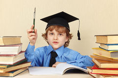 Young boy in academic hat with rarity pen among old books. Young boy in academic hat with rarity pen among the old books Stock Images