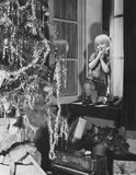 Young boy admiring Christmas tree and presents from window Royalty Free Stock Images