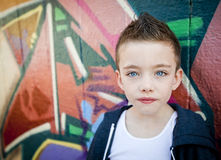 Young boy against graffiti wall Stock Photo