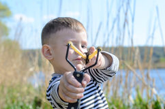 Young Boy Aiming Sling Shot at Camera Royalty Free Stock Photos