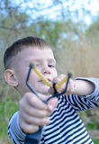 Young Boy Aiming Sling Shot at Camera Stock Photos