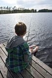 Young boy angling. Young boy on bridge angling in a lake Royalty Free Stock Images