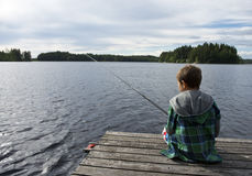 Young boy angling. Young boy on bridge angling in a lake Royalty Free Stock Photography