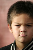 Young Boy Angry. Young boy with a serious scowl expression. Could be mad, angry, unhappy or just pissed Royalty Free Stock Photo