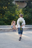 A young boy is approaching to the girl with flowers Royalty Free Stock Photo
