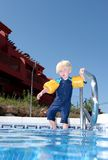 Young boy with arm bands climbing into swimming pool Stock Images