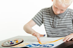 Young boy artist doing finger painting Stock Photos