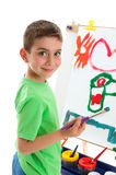 Young boy artist painting at easel Royalty Free Stock Photo