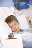 Young boy asleep in hospital bed Stock Images
