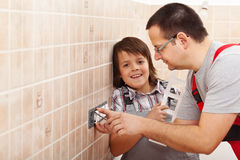 Young boy assisting his father installing electrical wall fixtures. Boy assisting his father installing electrical wall fixtures - holding front panel, copy royalty free stock photos