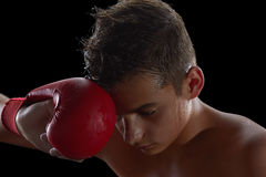 Young boy athlete, boxer or kickboxer gloves after training. Young boy athlete, boxer or kickboxer gloves after losing or training. Black background Stock Photography