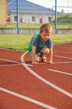 Young boy on athletic stadium. Young boy on a running track of an athletic stadium, waiting for start Stock Images
