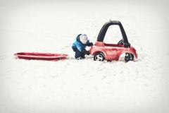 Young Boy Attaching a Red Sled to his Toy Car Stock Photos
