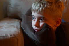 Young boy with attentive look. Boy watching off frame television with attentive gaze Royalty Free Stock Image