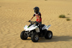 Young Boy in ATV. Young Boy Quad Biking in the desert Stock Photo