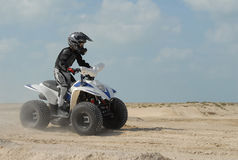 Young Boy in ATV. Young Boy Quad Biking in the desert Royalty Free Stock Image