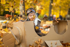 Young boy in autumn park in a pasteboard airplane. Vibrant autumn background Stock Images
