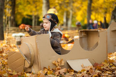 Young boy in autumn park in a pasteboard airplane. Vibrant autumn background Stock Photography