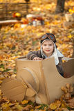 Young boy in autumn park in a pasteboard airplane. Vibrant autumn background Royalty Free Stock Photos