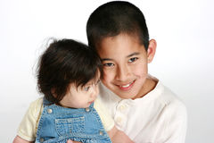 Young boy with baby sister. Young boy holding his baby sister stock photos