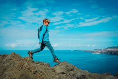 Young boy with backpack hiking in mountains at sea royalty free stock photo